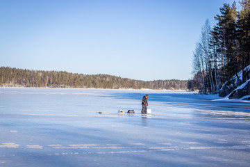 Boy at the winter fishing on frozen lake