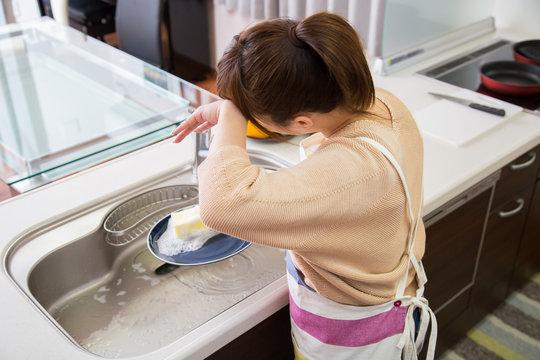 食器を洗う疲れた女性