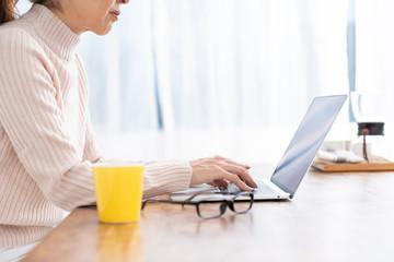 ラップトップコンピューターを見るシニア女性 手元