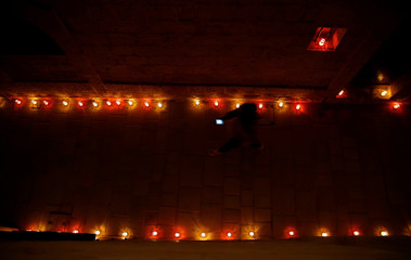 A visitor uses a mobile phone while walking through a candlelit street during the Festival of Lights Cittadella, in the medieval citadel in Victoria, on the island of Gozo