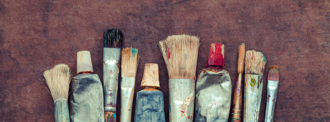 Artist paint brushes, paint tubes closeup on canvas. Copy space for text.