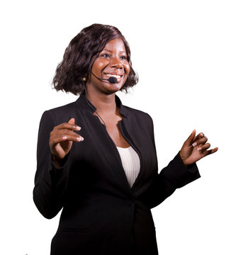attractive confident business woman with microphone headset speaking to audience in auditorium at corporate event seminar in motivation and success coaching conference
