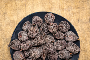 dried mission figs on black plate