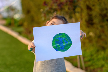 Portrait of the cute little girl holding the drawing earth globe. Child drawing a picture of earth.Earth day, plastic free and zero waste concept.