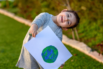 Portrait of the cute little girl holding the drawing earth globe. Child drawng a picture of earth.Earth day, plastic free and zero waste concept.