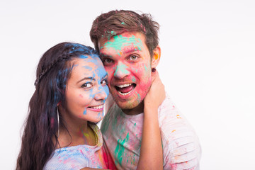 Holiday, holi and people concept - Smiling funny woman and man posing with multicolored powder on their faces on white background