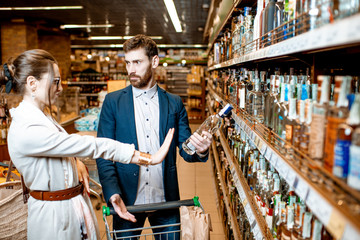 Man choosing strong alcohol, standing with his dissatisfied wife in the supermarket