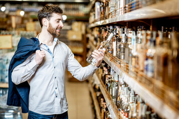 Portrait of a man with a thirst for alcohol, standing near the shelves with strong drinks in the supermarket
