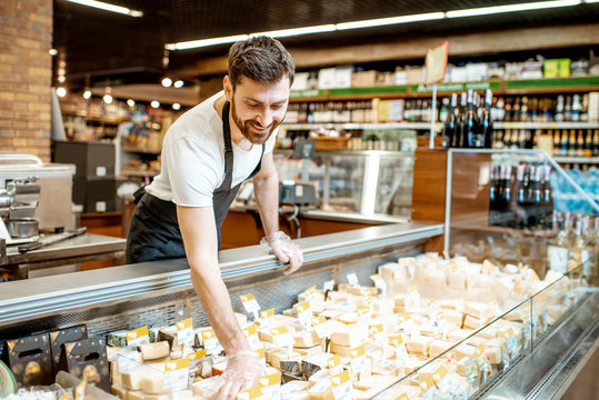 Shop worker laying out cheese pieces into the refrigeration showcase in the supermarket