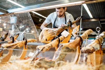 Handsome seller slicing jamon on the counter with dried meat in the supermarket