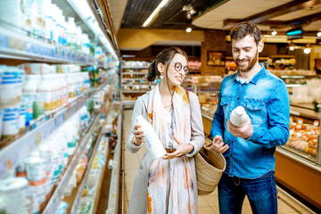 Young couple choosing milk standing together near the shelves with dairy products in the supermarket