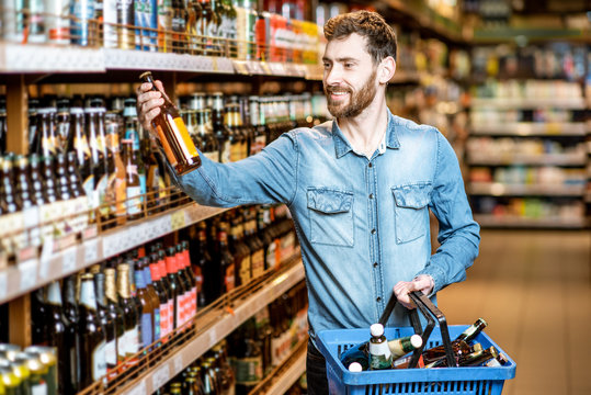 Man with thirst to alcohol taking beer from the shelves with strong drinks in the supermarket