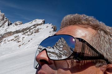 Mann Blickt auf die verschneiten Berge