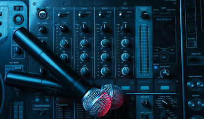 Night club, nightlife concept. Disco. Two microphone on DJ remote. Neon red blue light