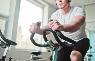 Healthy lifestyle concept. Young sporty man in white t-shirt and shorts is exercising bike at spinning class . Cardio training