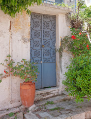house entrance metallic door and flowers, Athens Greece, Anafiotika neighborhood