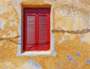 deep red window shutters on weathered colorful wall, Athens Greece, Anafiotika neighborhood
