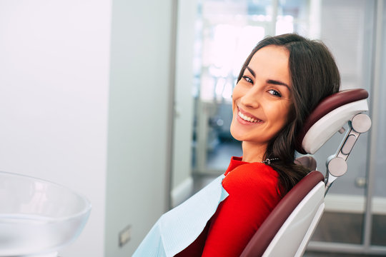 New life with new teeth.  Gorgeous girl wearing red sweater in the stomatology room full of day-light and white colors is smiling with her new  white eye-catching smile.