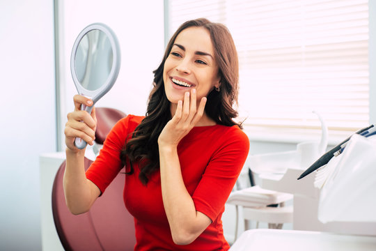 Long-term result. Nice looking girl in scarlet sweater is holding a mirror in her elegant hand and looking through the perfect  result of the dental work.