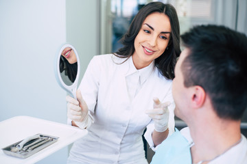Stress-free dentistry. Calm dental doctor is wearing special clothes and holding a mirror in her hand to show to the satisfied patient the results of her work.