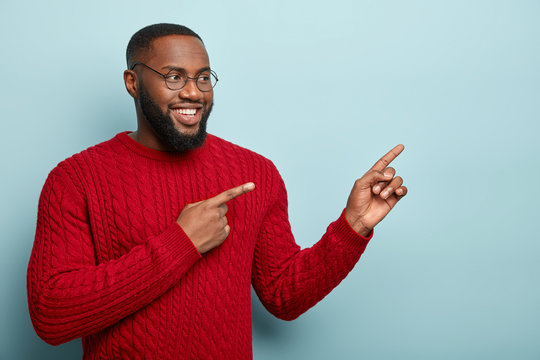 Waist up shot of satisfied bearded adult man advertises new promo of store, points right sees something really attractive, wears round optical spectacles and red jumper, grins at camera. Look here!