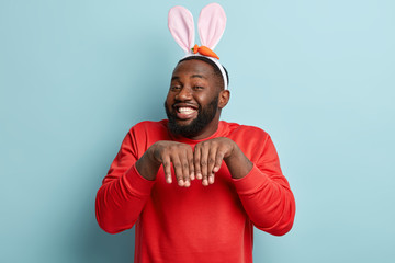 I am Easter bunny. Cheerful smiling dark skinned man with toothy broad smile, imitates rabbit, looks playfully, tries to amuse children, keeps hands likes paws, stands against blue background