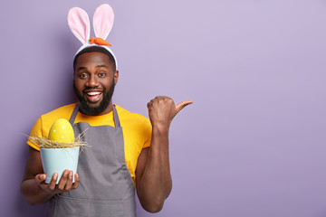 Plump glad Afro American man points away with thumb, glad to advertise something, holds pot containing egg, decorates with colorful paints, isolated over lilac studio wall. Easter traditions concept