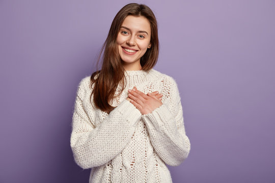 Friendly pleased woman has heart filled with love and gratitude, keeps both hands on chest, has lovely sincere smile, wears oversized jumper, stands against purple background, sympatizes friend