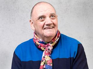portrait vieil homme au grand sourire sur fond gris