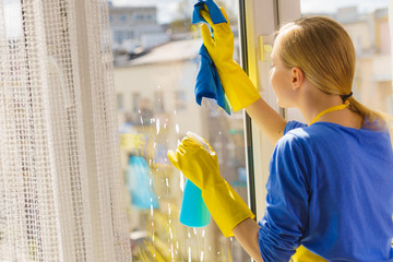Woman cleaning window at home
