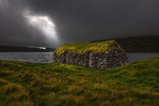 Turf roof stone dwelling situated on the shore of the sea, Faroe Islands