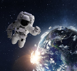 Flying astronaut operating nearby of planet Earth.