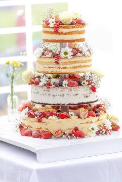 bunte Hochzeits -Torte mit Blumen und Beeren