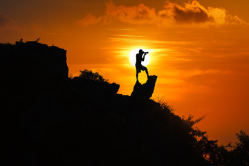 Silhouette of photographer on top of mountain at sunset red sky background