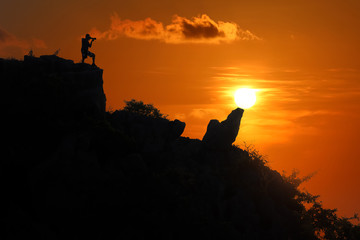 Silhouette of photographer on top of mountain at sunset red sky