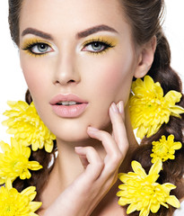 face of an young beautiful woman with bright yellow make-up.