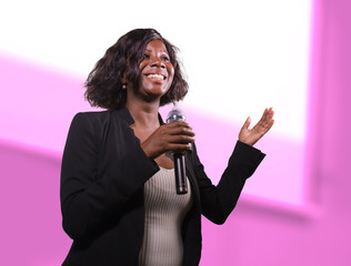 confident black afro American business woman with microphone speaking in auditorium at corporate event or seminar giving motivation and success coaching