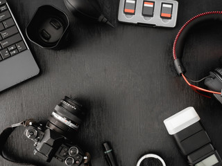 top view of work space photographer with digital camera, flash, cleaning kit, memory card, external harddisk, USB card reader, laptop and camera accessory on black table background