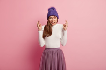 Displeased woman frowns face and clenches teeth, has fingers crossed, believes in good fortune, wears stylish winter outfit, wants dreams come true, stands over rosy background. Female prayer