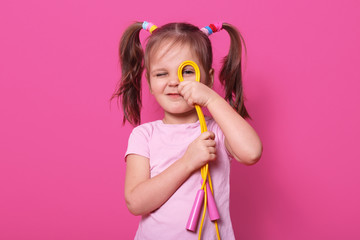 Portrait of emotional beautiful girl, wears rose t shirt with two pony tails. Charming kid looks...