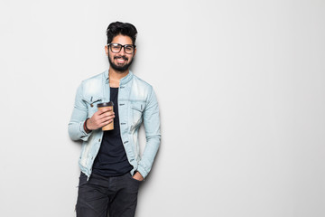 Taking a coffee break. Handsome young Indian man holding coffee cup and smiling while standing against white background