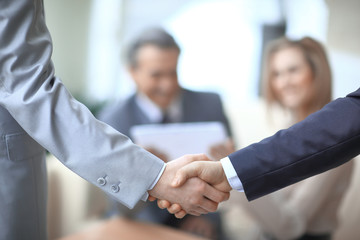 close up.handshake of business partners on the background of the workplace