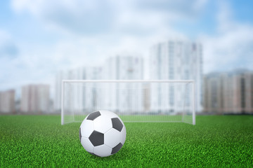 3d rendering of football ball, gate and field with city buildings on the background
