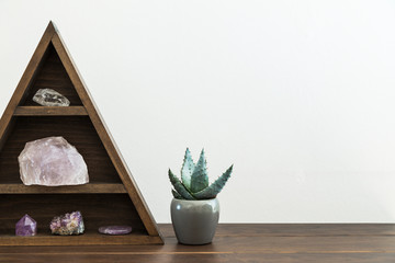 Triangular Crystal Shelf on a Wooden Surface with Potted Succulent Plant