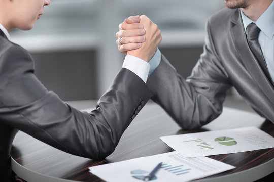 close up. two businessmen are engaged in arm wrestling at a Desk