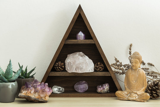 Triangular Crystal Shelf with Succulent Plants Foliage and Wooden Statue of Buddha