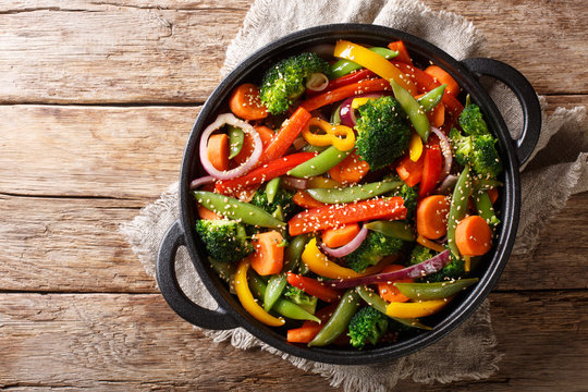 Healthy Asian food stir fry of vegetables with sesame close-up in a bowl, horizontal top view