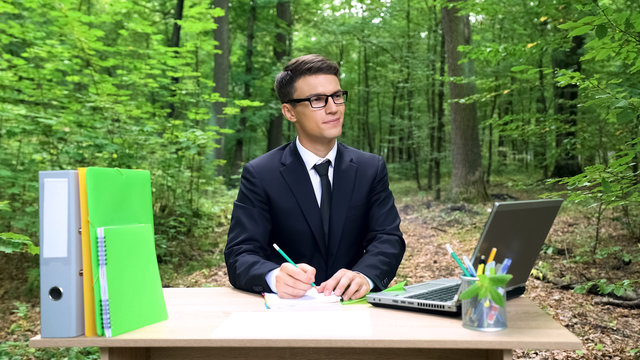 Young businessman writing good ideas, working at office desk in green forest