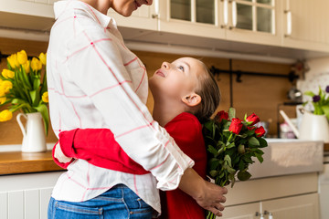 Happy Mother's Day or Birthday Background. Adorable young girl hugging her mom after surprising her with bouquet of red roses. Family celebration concept.