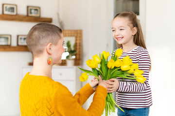 Happy Mother's Day or Birthday Background. Adorable young girl surprising her mom with bouquet of yellow tulips. Family celebration concept.